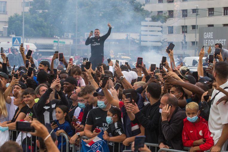 PSG-fans proberen bij het vliegveld Le Bourget een glimp op te vangen van hun idool Messi. Beeld EPA