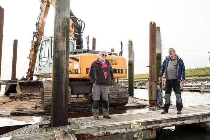 Coördinator baggerwerkzaamheden Peter Mater van Watersportvereniging Zierikzee (links) en voorzitter Alphons Drübers van Watersportvereniging Zierikzee op de steiger bij het deel van de jachthaven waar maandag het werk is begonnen