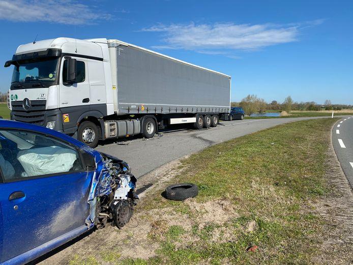 Een zwaar beschadigde auto, het resultaat van een klap tegen de geparkeerde vrachtwagen langs de dijk tussen Olst en Deventer.
