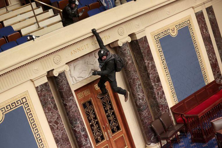 Een relschopper bungelt aan het balkon van de Senaat. Beeld AFP
