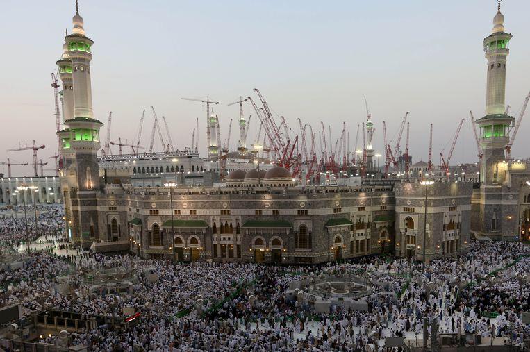 Op de achtergrond van de grote moskee schieten tientallen hijskranen de lucht in. Beeld AP