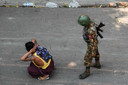Een militair arresteert een demonstrant.