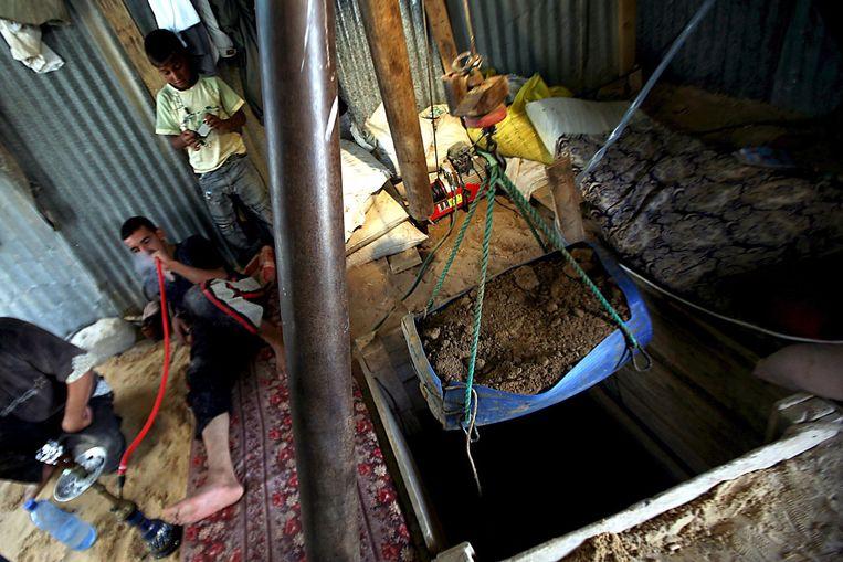 Een Palestijnse man rookt waterpijp voordat hij verder gaat met het graven van een nieuwe tunnel. Beeld null