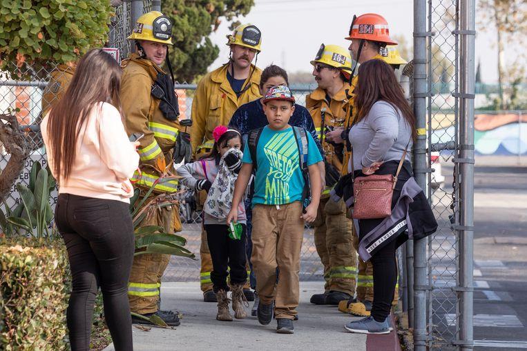 Scholieren worden opgehaald door hun ouders, terwijl brandweermannen toekijken in het plaatsje Cudahy.  Beeld EPA