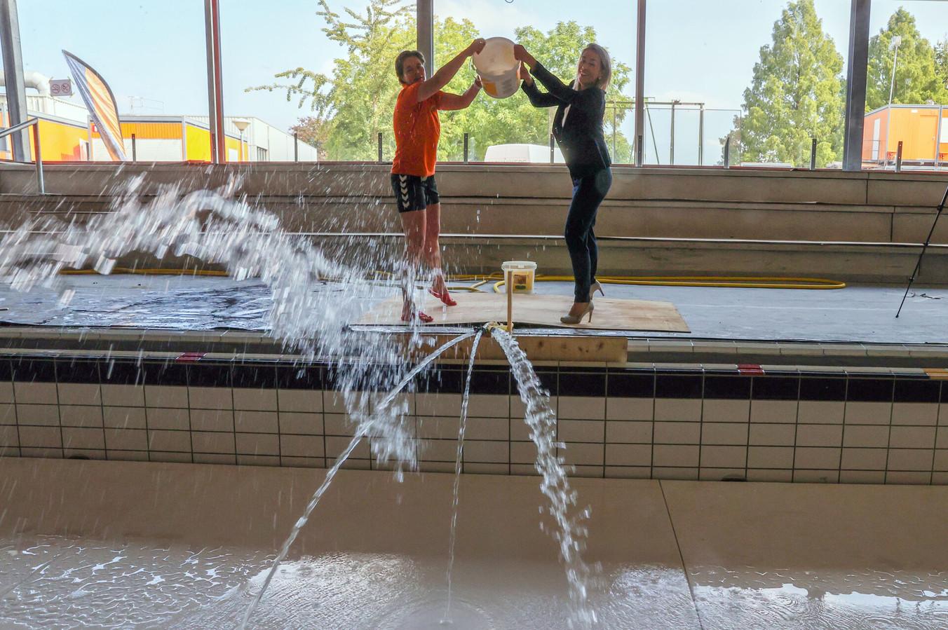 Zwembad-directeur Minette Lommers (links) en wethouder Vivianne van Wieren-Kraayvanger legen een emmer water in het grootste bad van het nieuwe City Sport Veldhoven.