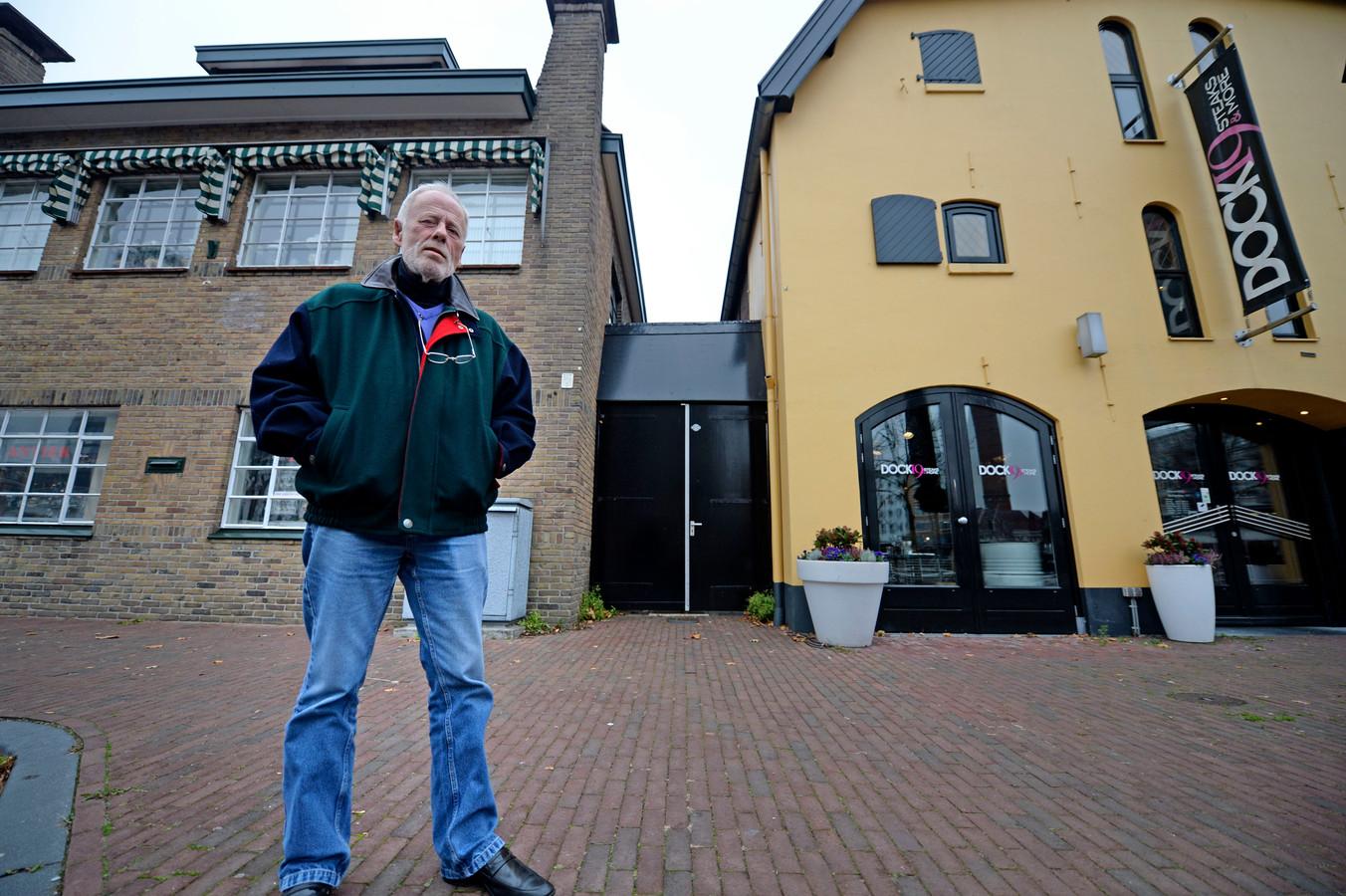 Antiekhandelaar Henk Stegehuis bij de poort tussen zijn winkel en het naastgelegen restaurant.