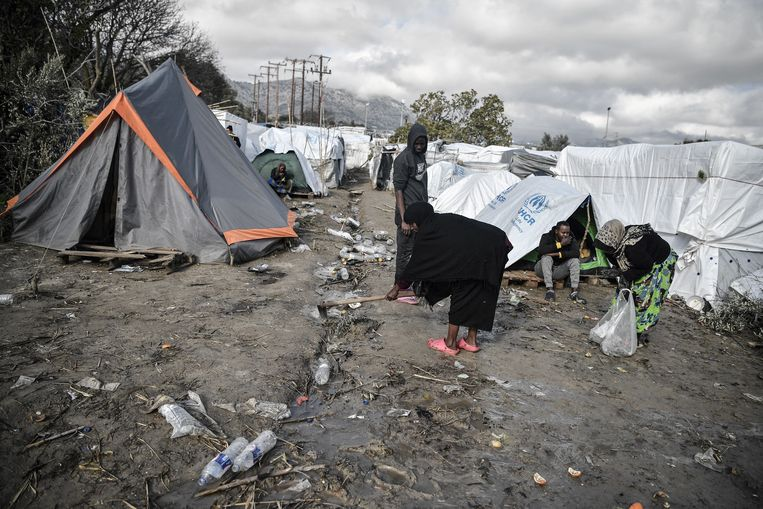 In het kamp op Chios probeert een vrouw  het pad schoon te maken. Beeld Hollandse Hoogte / AFP