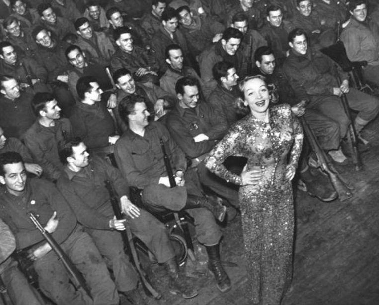 Actrice Marlene Dietrich (40), in een avondjurk met pailletten, bij een optreden voor soldaten in 1941.    Beeld The LIFE Picture Collection via