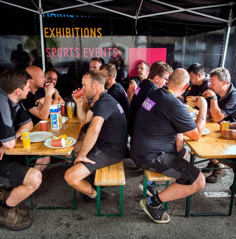 Zodra de laatste renner de streep over is, begint deze crew aan hun dagelijkse monsterklus. Beeld Klaas Jan van der Weij / de Volkskrant