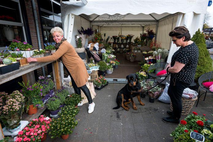 Gera van Bloemenboutique Nicole (l) kan haar hoofd boven water houden doordat ze buiten bloemen verkoopt.