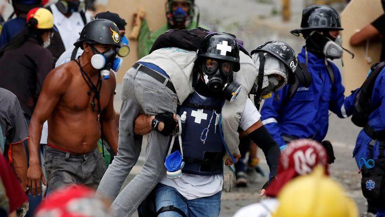 Een gewonde demonstrant wordt geholpen tijdens een demonstratie tegen het beleid van President Nicolas Maduro. Beeld reuters