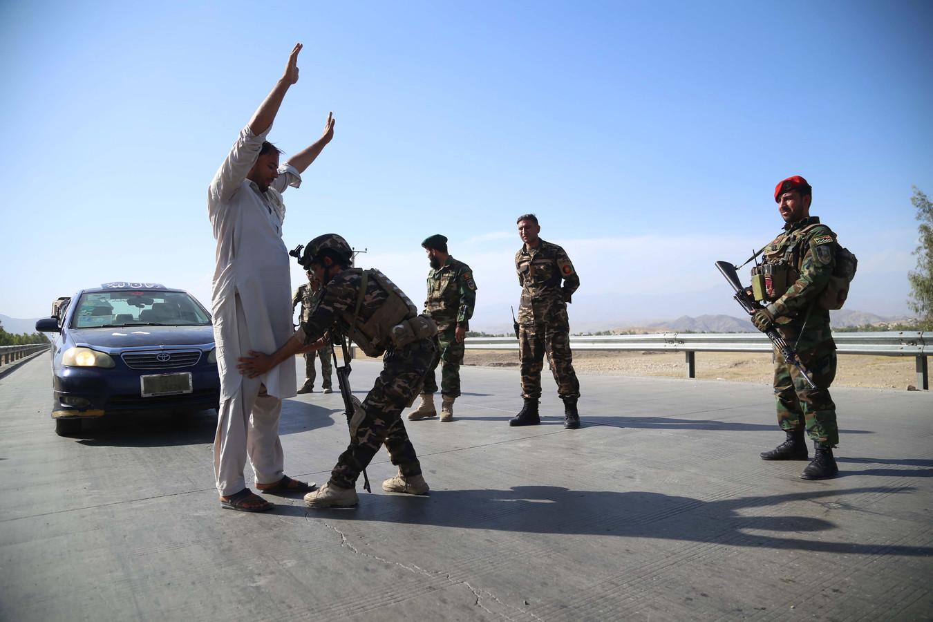 Het Afghaanse leger fouilleert voorbijgangers bij Jalalabad.