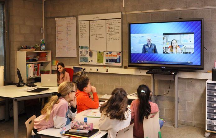 Sofia Fiorito (9) stelt achter de laptop van de juf haar vraag aan André Kuipers, terwijl klasgenoten van basisschool De Driestam in Eindhoven toekijken.