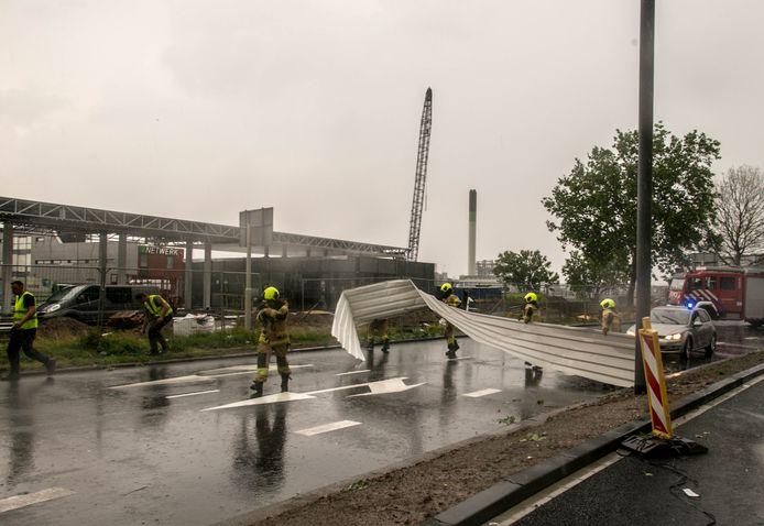 Dakplaten nieuwe BP vliegen over de weg achteruit auto beschadigd en bij Praxis boom op busje