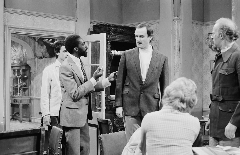 (V.l.n.r.) Louis Mahoney, John Cleese en Willy Bowman in de aflevering 'The Germans' van 'Fawlty Towers', 1975.   Beeld Radio Times via Getty Images