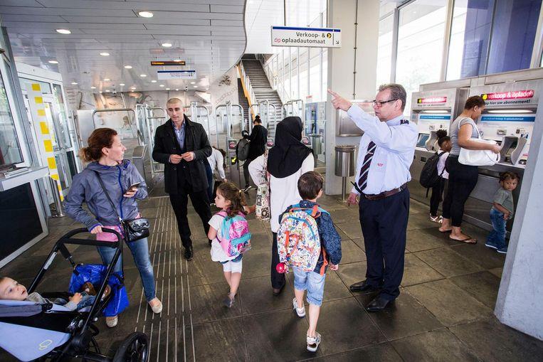 Trambestuurder André den Exter helpt donderdag, zoals hij elke week een dag doet, reizigers op de perrons van de RET in Rotterdam. Beeld Arie Kievit