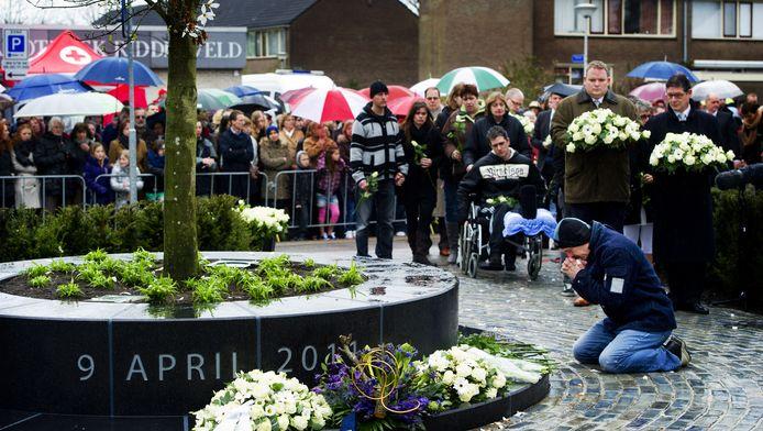 Een belangstellende knielt tijdens een herdenking, een jaar na de schietpartij.