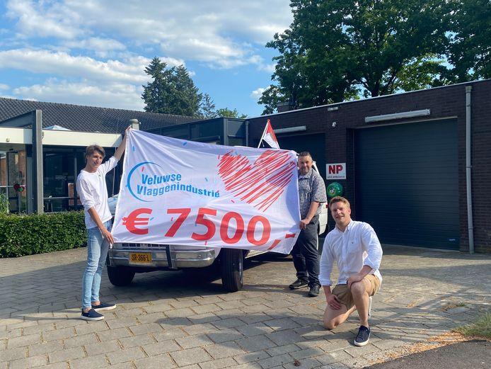 De mannen van de Veluwse Vlaggenindustrie brengen hun vlag en het bedrag bij het Rode Kruis in Apeldoorn.