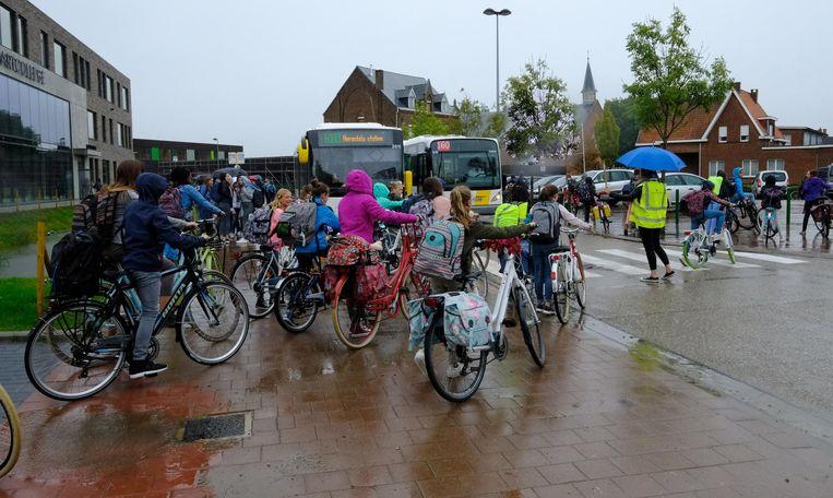 Bussen wachten terwijl leerlingen de school verlaten.