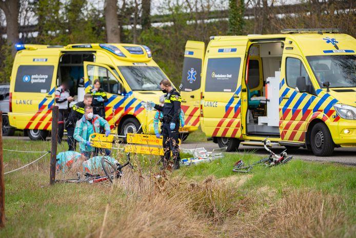 Hulpverleners buigen zich over de gewonde wielrenner. Hij werd uiteindelijk per traumahelikopter vervoerd naar het ziekenhuis.