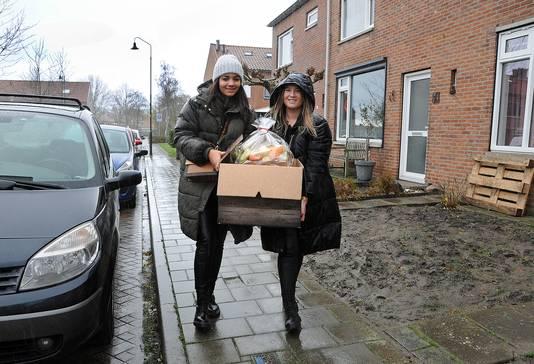 Amy Johnson (l) en Laura Lafranca delen donderdagmiddag pakketten voedsel en andere boodschappen uit aan vluchtelinggezinnen op Schouwen-Duiveland.