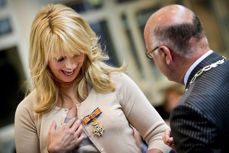 Presentatrice en actrice Linda de Mol ontvangt vrijdag in Huizen een  koninklijke onderscheiding uit handen van waarnemend burgemeester Fons  Hertog. De Mol werd bevorderd tot Officier in de Orde van Oranje-Nassau. Foto ANP.<br /> Beeld
