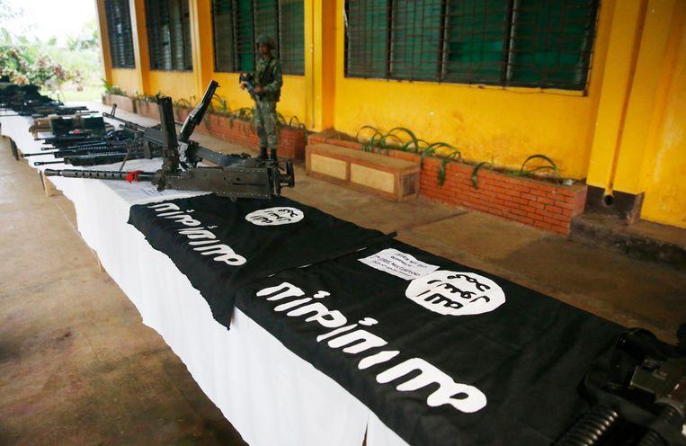 Door het Filipijnse leger in beslag genomen vuurwapens en vlaggen van IS in Marawi. Beeld AP