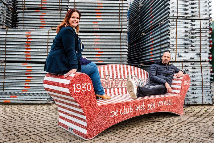 Annet Verpoort  en Mark de Feijter zijn enthousiast over de nieuwe jubileumbank, die een ereplaats krijgt op het terras van Alphense Boys.