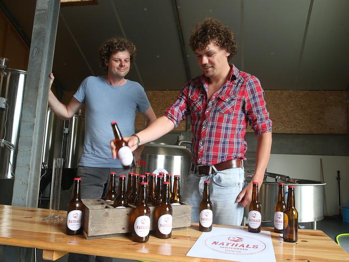 Brouwer Geerart van Doorn (links) en creatief brein Tijn Spekkink bekijken tevreden de eerste met Nathals bier gevulde flesjes.