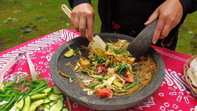 Wahyu in volle actie. Ze mengt alle ingrediënten zorgvuldig door elkaar.
