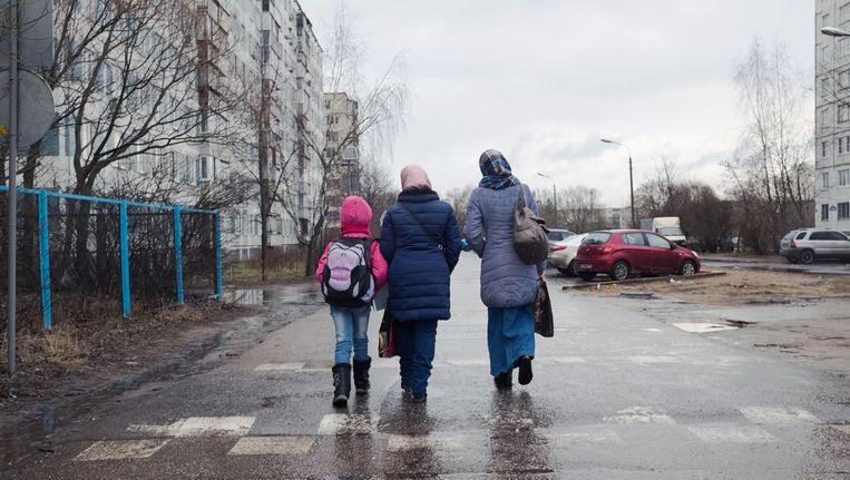 Moeder en dochter keren terug van school, bijgestaan door een lokale vrouw (R) - een Russische moslima. Scholing vinden voor vluchtelingen blijkt erg moeilijk in Rusland. Beeld Arthur Bondar