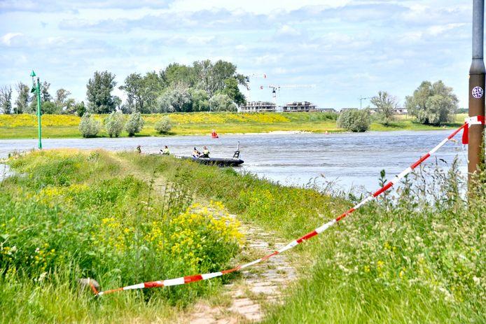 De politie onderzoekt het gevonden lichaam in de Waal bij Nijmegen.