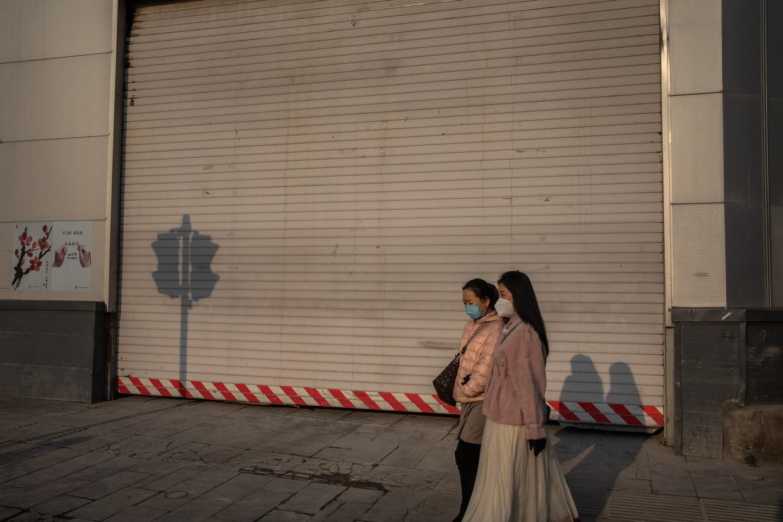 Twee vrouwen 's avonds op straat in Peking.