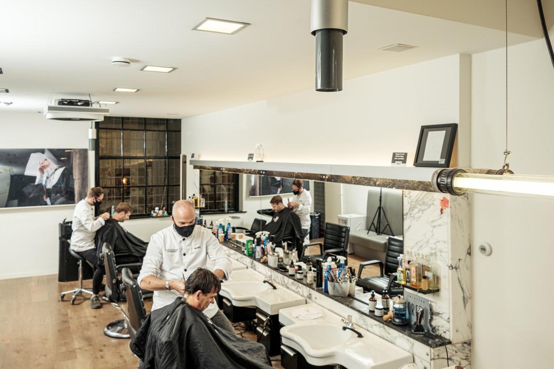 Marc van de Hare heeft een ionisator aan het plafond gehangen in zijn barbershop. 'De lucht is binnen nu schoner dan buiten.' Beeld Jakob Van Vliet