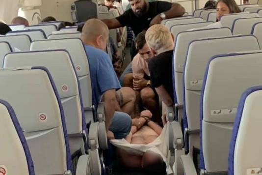 De dronken vechtersbaas wordt door passagiers en crew in bedwang gehouden.