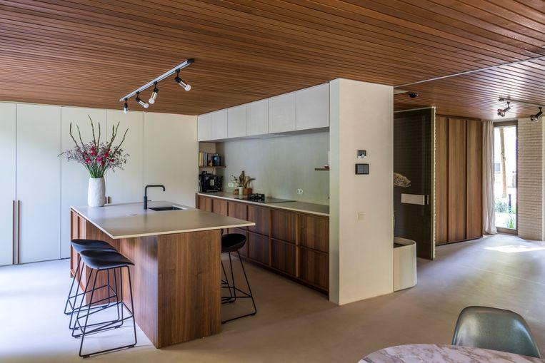 De zandkleurige keuken met kasten van notelaar vormt een mooie match met het gerestaureerde plafond van cederhout.  Beeld Luc Roymans