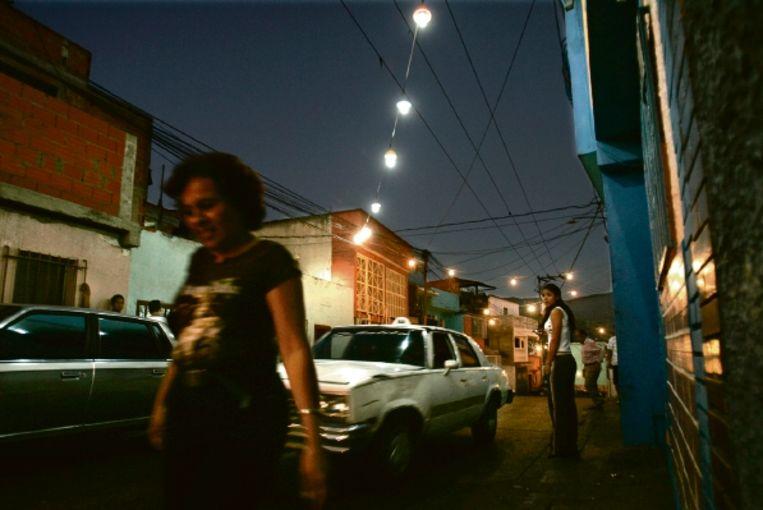 Voetgangers in de Venezolaanse hoofdstad Caracas. In de straat hangen door de overheid in 2007 verstrekte energiezuinige lampen. ( FOTO AP) Beeld ASSOCIATED PRESS
