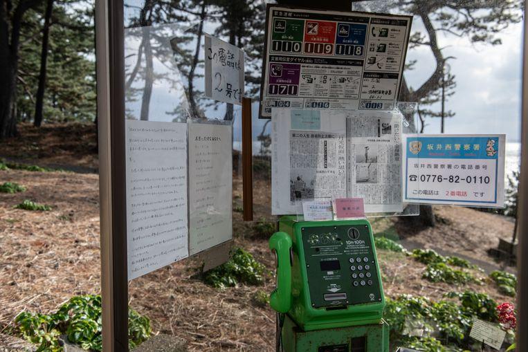 Een telefooncel in Tojinbo, Japan, met telefoonnummers van suïcidepreventie en bijbelteksten. Beeld Getty Images