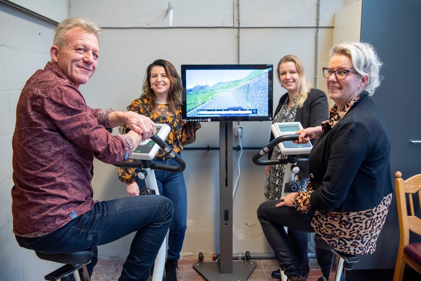 Op een hometrainer kunnen ouderen ook visueel over fietsen waar ze willen. Vlnr: vader Klaas, dochters Tamar en Marlon en moeder Herma Kuiper.