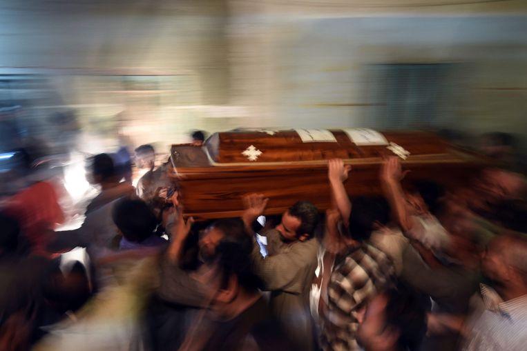 Nabestaanden van de vermoorde gelovigen dragen de doodskisten naar de kathedraal in Maghagha. Beeld AFP