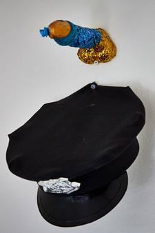 Glitterdildo en politiepet aan de muur als stil protest tegen zich misdragende agenten