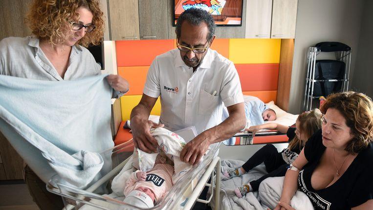 Gynaecoloog Richard Pal en een verloskundige bekijken een pasgeboren baby in het Bravis Ziekenhuis in Bergen op Zoom. Beeld Marcel van den Bergh