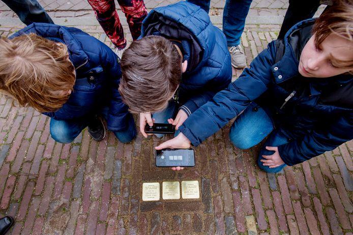 Scholieren maken in Oisterwijk met hun mobieltjes een foto van struikelstenen, die herinneren aan Joodse slachtoffers van de Holocaust.