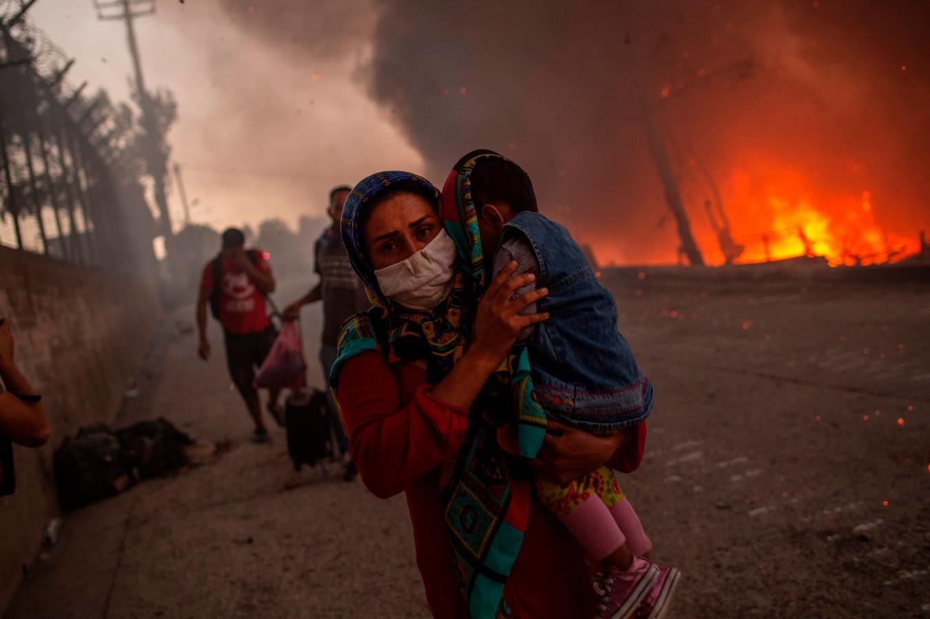 Een vrouw draagt haar kind tijdens de brand in kamp Moria.
