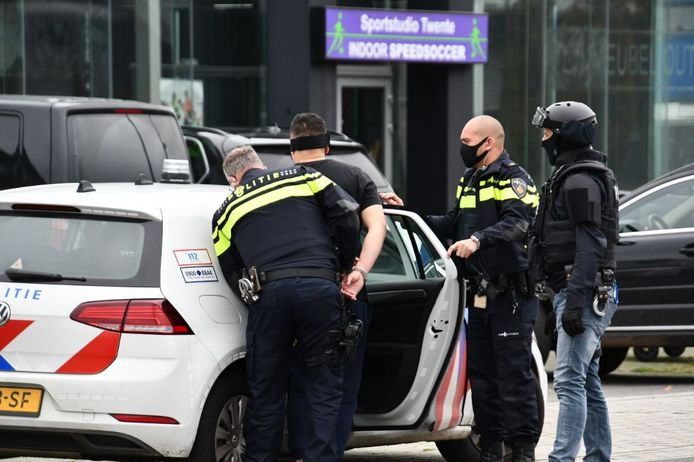 Een van de verdachten wordt geblinddoekt door de politie gearresteerd.