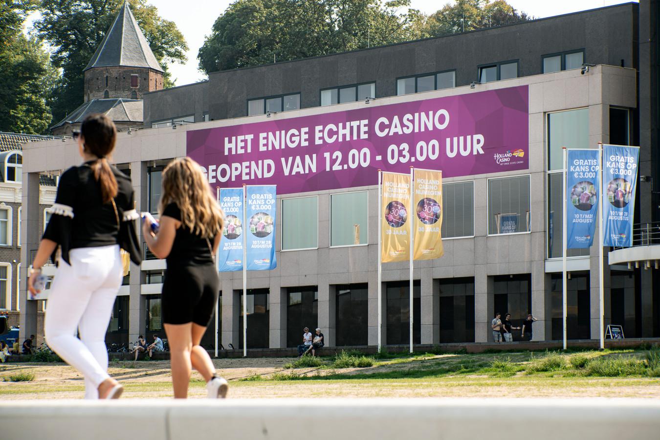 Holland Casino aan de Waalkade adverteert op de gevel met een enorm spandoek en met banners aan vlaggenmasten.