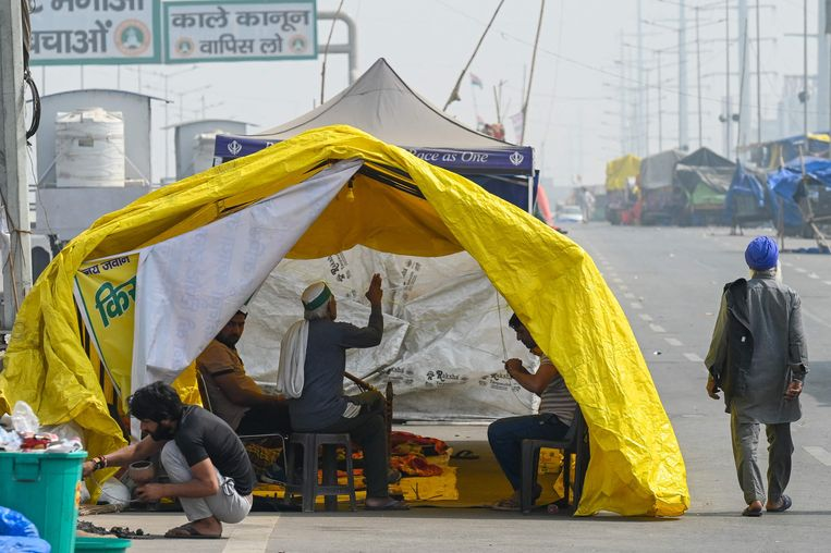 Protesterende boeren rusten in een tent langs de snelweg, waar ze protesteren tegen de landbouwhervormingen van de regering.  Beeld AFP