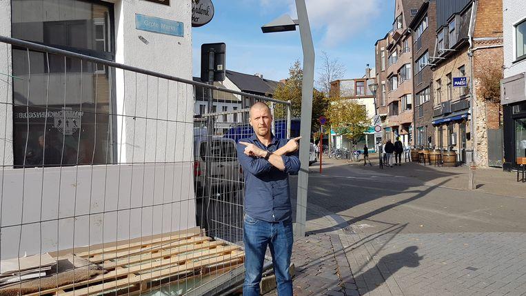 Tom Antonis voor het pand op de Grote Markt en op de achtergrond het pand van De Zwarte Ruiter, dat gesloopt wordt en vervangen door een nieuwbouw.