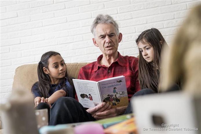 """Frans Hijman, vrijwilliger van de VoorleesExpress leest Naomi (links) en Joann voor. """"Ik merk dat ze vooruit gaan. Ze leren spelenderwijs heel veel nieuwe woorden."""""""