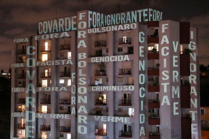Stil protest. Op een flatgebouw staan onder meer de woorden 'Bolsonaro weg', ' lafaard', ' fascist' en 'crimineel'  geprojecteerd.